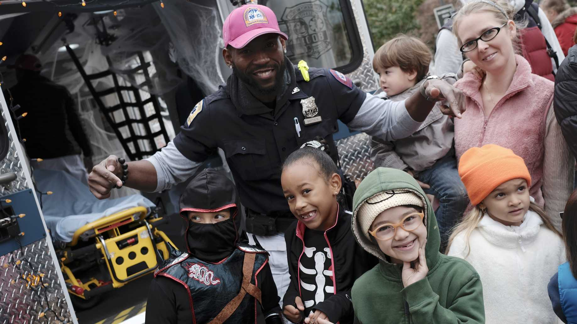 NewYork-Presbyterian EMT poses with kids participating in LC Kids Trick-or-Treat Event